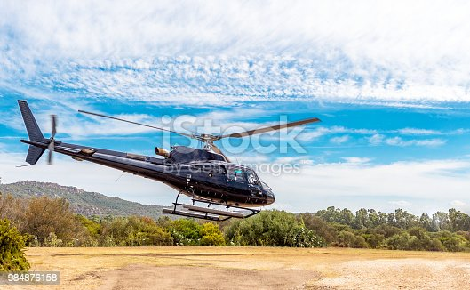 Horizontal color image of helicopter on airfield. Tour in Corsica.