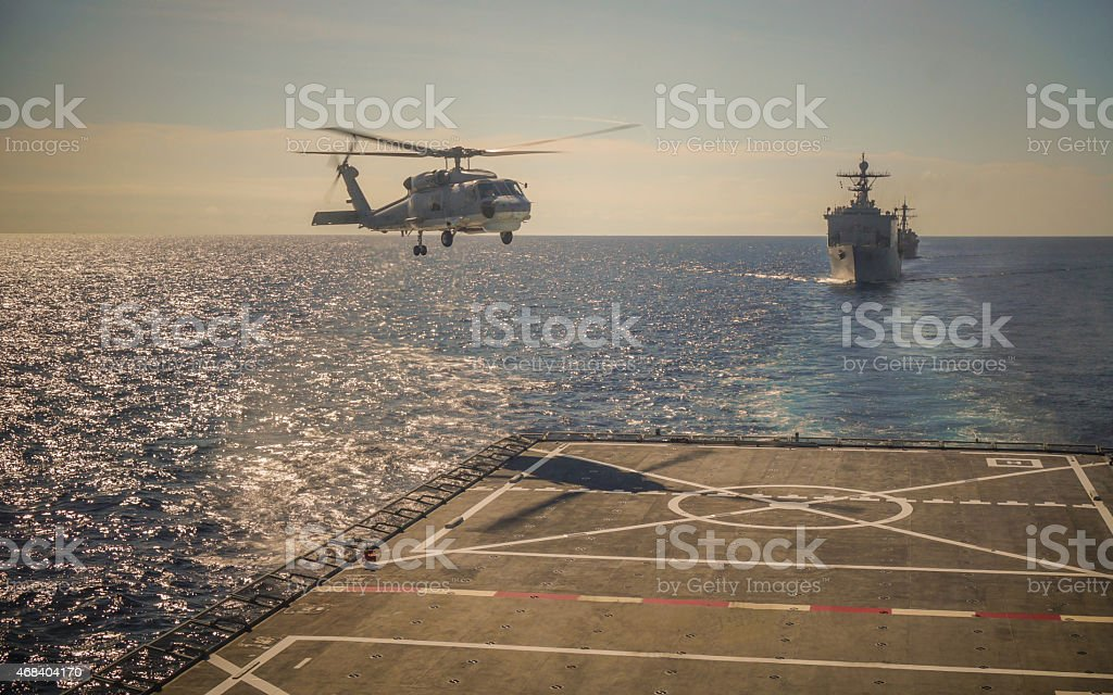Helicopter landing on warship stock photo