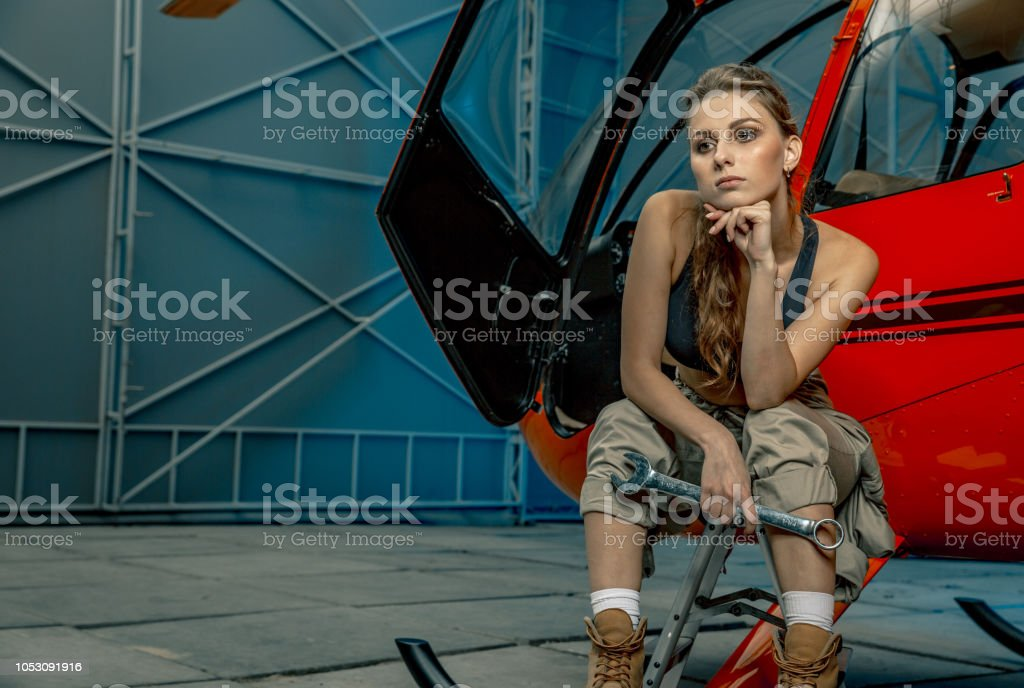 helicopter maintenance femail worker. woman pilot or helicopter mechanic holding the adjustable wrench. stock photo