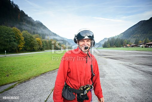 A helicopter mountain rescue paramedic standing on the runway of an aerodrome in the Swiss Alps, Bernese Oberland region.