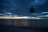 Helicopter flies over the water surface against the background of the setting sun over the horizon