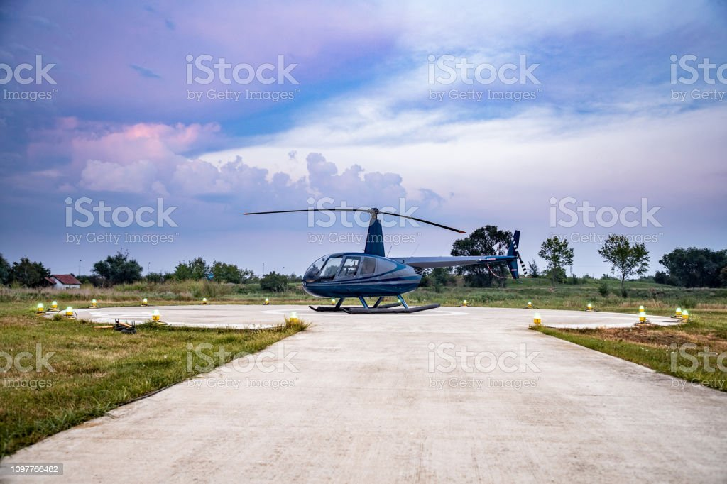 Helicopter On Helipad With Landing Lights On At Dusk Stock Photo