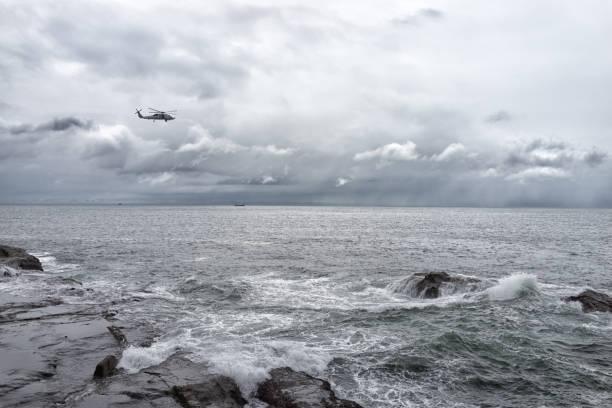 helicopter over seaside - rettungsinsel stock-fotos und bilder