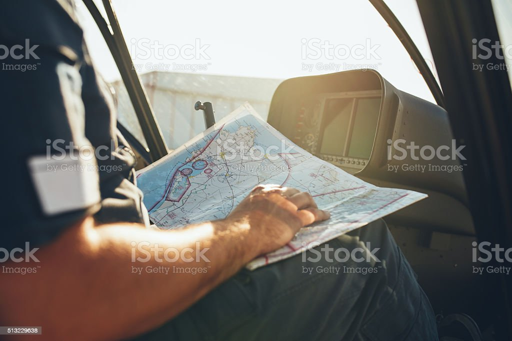 Helicopter pilot studying the flight route map stock photo