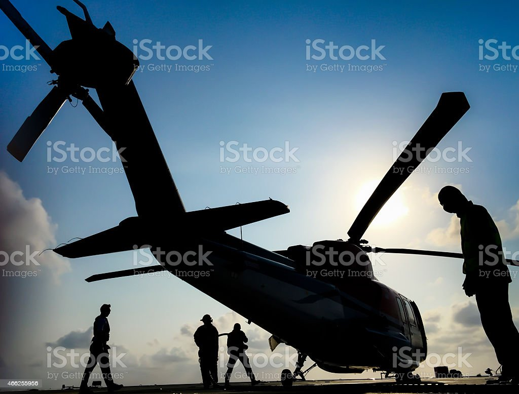 Helicopter refueling on an oil platform with shadows and sunrise stock photo