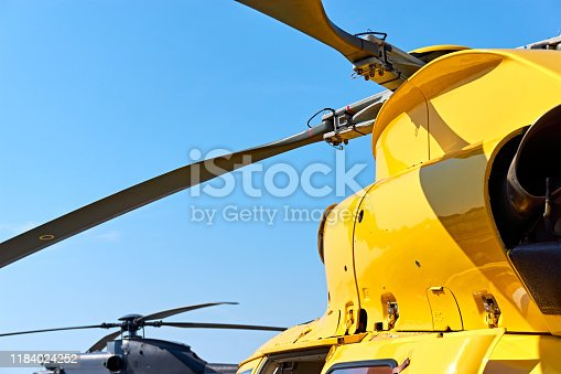 Yellow and black helicopter. Close up of helicopter main rotor blades against a blue sky with copy space.
