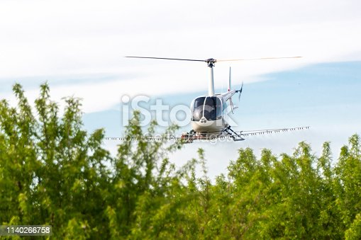 Flying Helicopter spraying insecticides over fruit trees