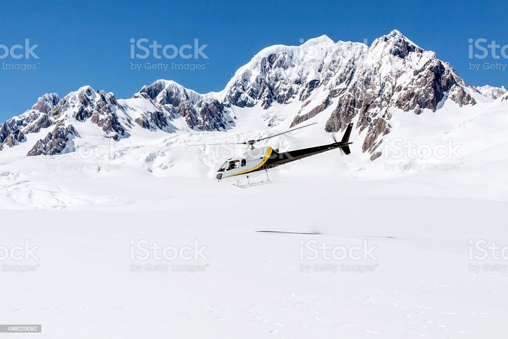 Helicopter Taking Off from a Snow Covered Mountain stock photo