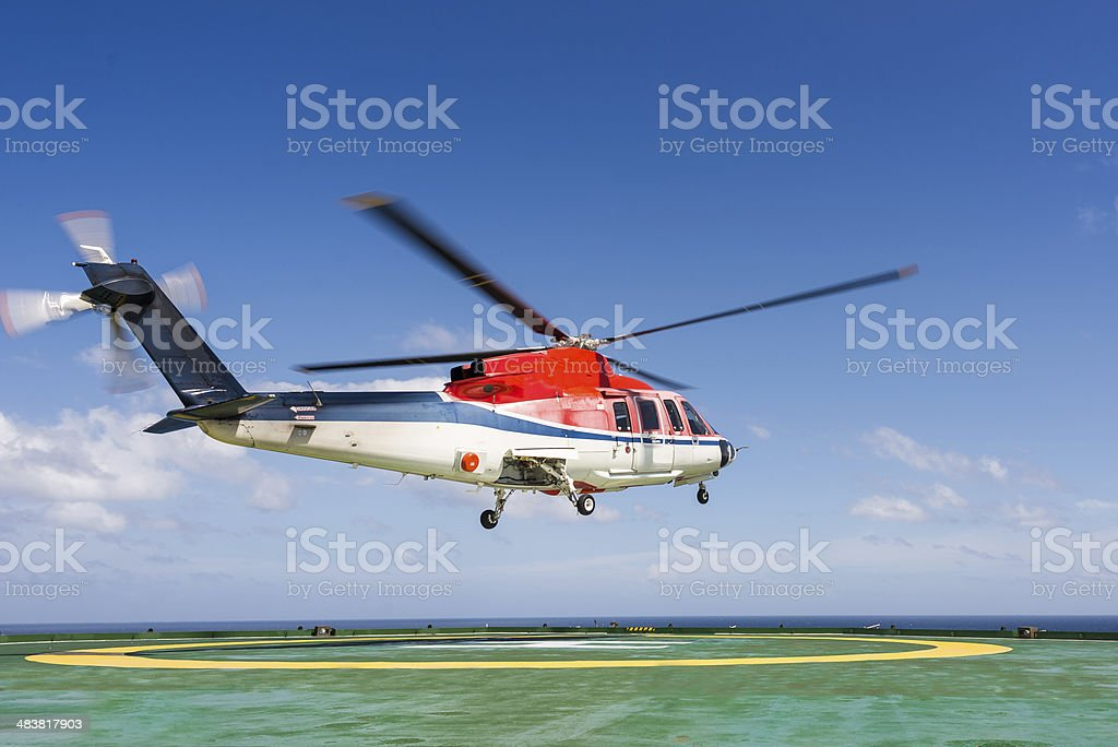 Helicopter taking off from jack up oil rig helipad stock photo