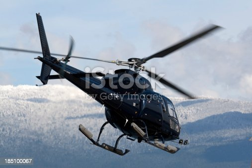 Close-up wide angle shot of a helicopter lifting off with a dramatic cloudy sky in the background.