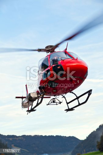 A red helicopter transports people through the Swiss Alps. Lenk Lypse 2012