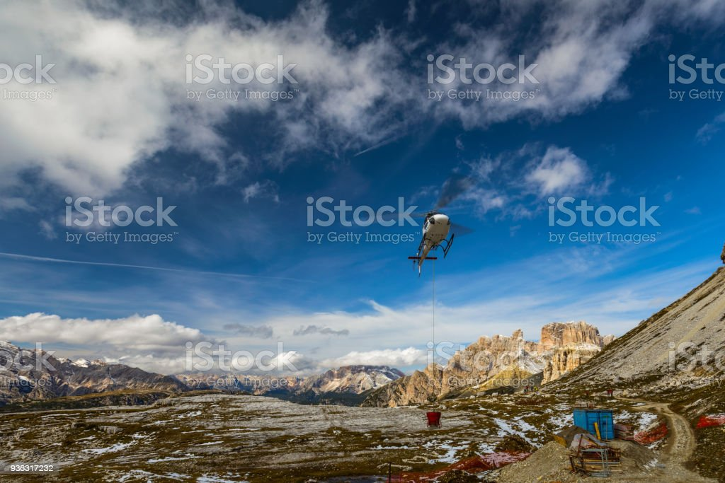 Helicopter used for rescue operations also for bringing construction materials, on the ground Tre Cime di Lavaredo in Dolomites, Italy. stock photo