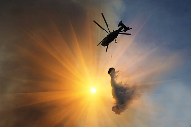 Helicopter waterbombs fire A lone helicopter waterbombs a fire at sunset. The rays of the sun are striking and penetrate the picture. The smoke creates a screen and the water streams out. smoke jumper stock pictures, royalty-free photos & images