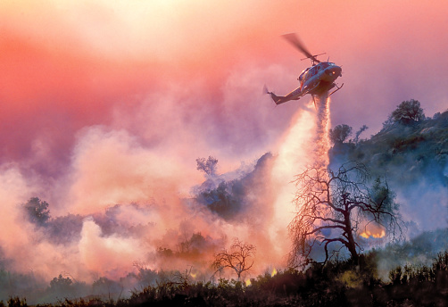 A helicopter dropping water on a California wildfire in rugged terrain, backlit by a setting sun filtered through multiple layers of smoke