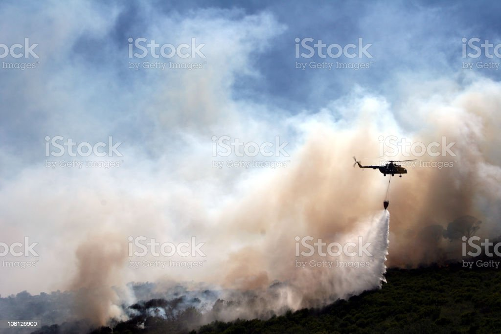 Helicopter with Water Over Forest Fire stock photo
