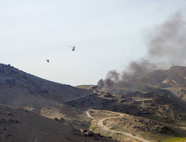 Helicopters flying over bombed Afghanistan landscape stock photo