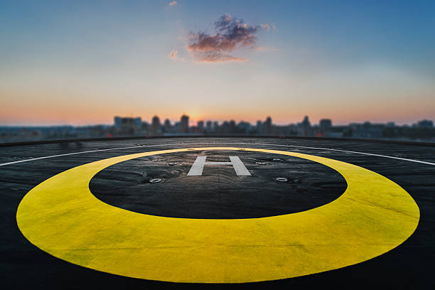 Helipad on the roof of a skyscraper with cityscape view Helipad on the roof of a skyscraper after raining with cityscape view and sunset airfield stock pictures, royalty-free photos & images