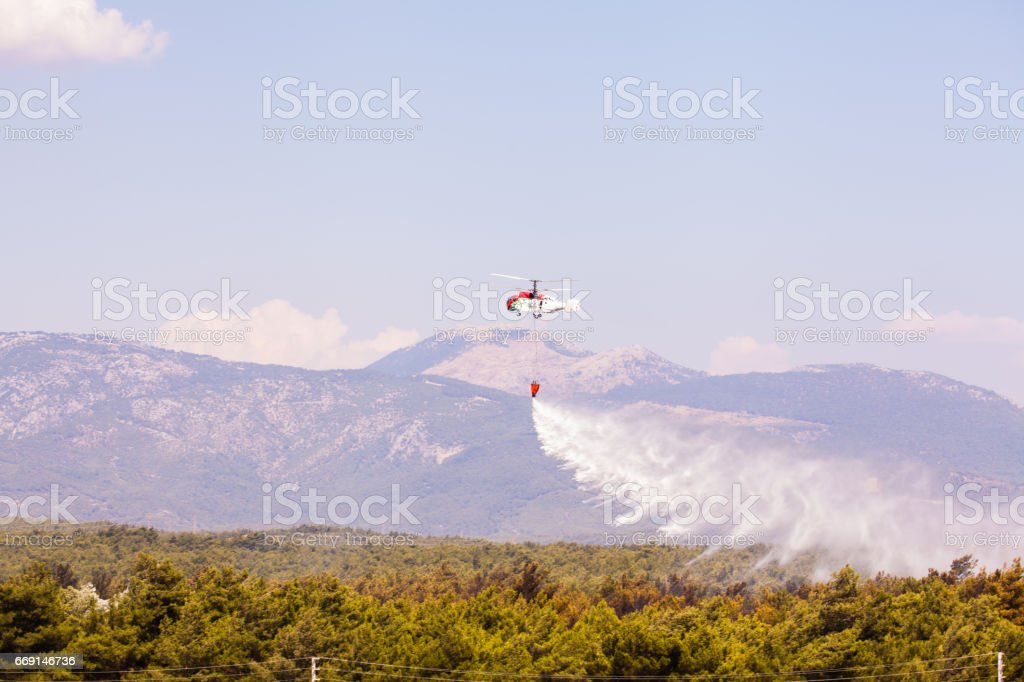 Helitack flying over a forest fire stock photo