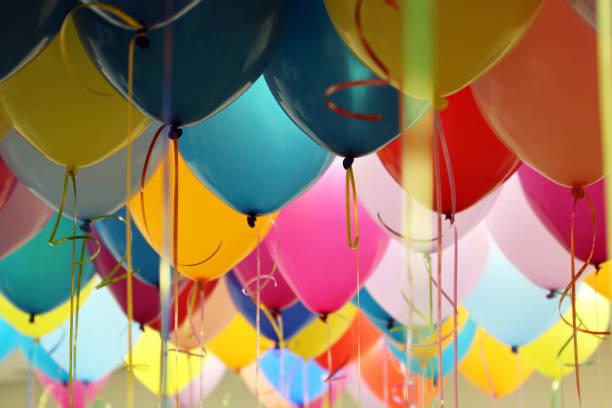 globos de helio con cintas en la oficina - fiesta fotografías e imágenes de stock