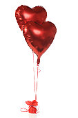 Two red, heart-shapped, helium-filled ballons anchored with red ribbons.  Isolated on white.