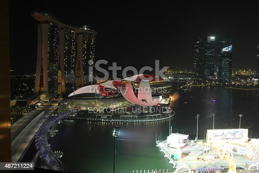 Singapore, Singapore - February 16, 2015: Night view of the pedestrian Helix Bridge, a structure of glass and stainless steel leading to the famous Marina Bay Sands Hotel. In the foreground are preperations for the Chines New Year.