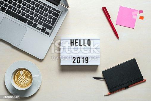 istock Hello 2019 written on lightbox in office as flatlay 918988642