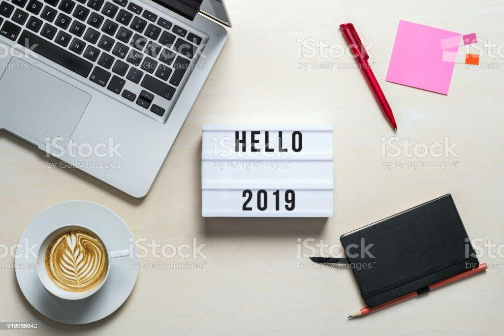 Hello 2019 written on lightbox in office as flatlay stock photo
