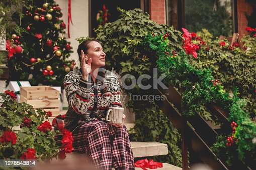 Front view of mature woman greeting a neighbour at the entrance of her house and drinking coffee after decorating for Christmas season.