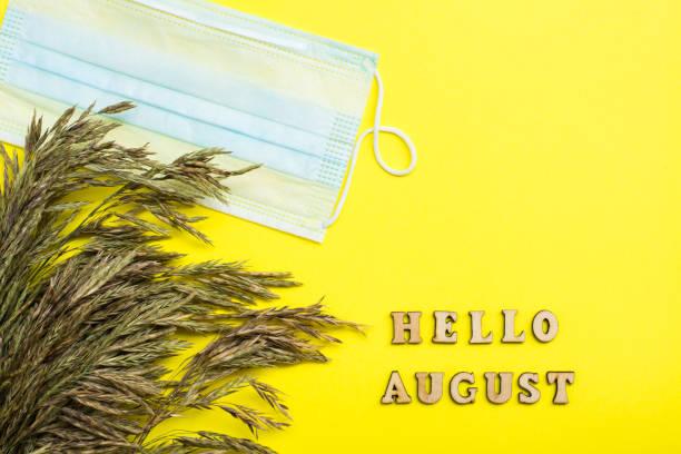 Merhaba August. Karantinada hayat. Ahşap harflerle metin, çim kulakları ve sarı bir arka plan üzerinde koruyucu bir maske stok fotoğrafı