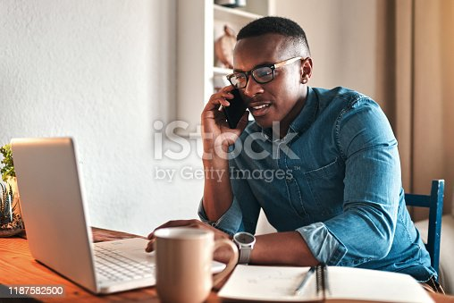Cropped shot of a handsome young businessman sitting alone in his home office and talking on his cellphone