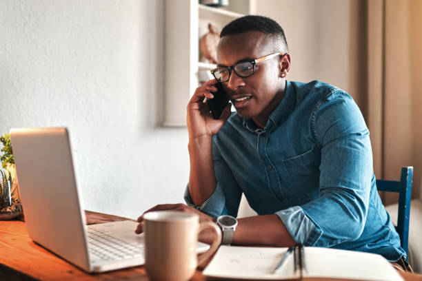 Hello, can I help you? Cropped shot of a handsome young businessman sitting alone in his home office and talking on his cellphone african american ethnicity stock pictures, royalty-free photos & images