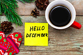 Hello December- handwriting in black ink on a sticky note with a cup of coffee and mittens, New Year resolutions concept