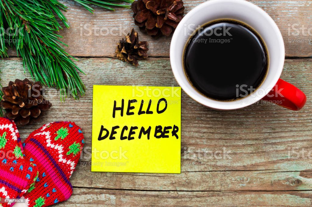 Hello December- handwriting in black ink on a sticky note with a cup of coffee and mittens, New Year resolutions concept stock photo