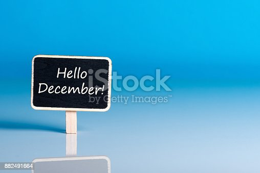 istock Hello december on sign at blue background with empty space for text, mockup. December 1st, the beginning of the Christmas and New Year holidays and sales 882491664