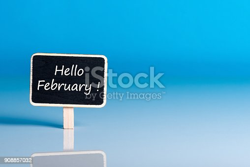 istock Hello February words on little wooden tag at blue background with empty space for text, template or mockup 908857032