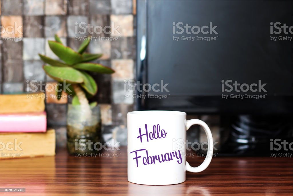 Hello February written on white coffee cup concept stock photo