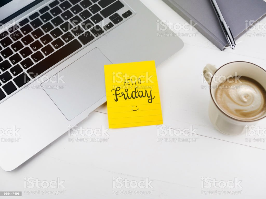 Hello Friday with smiley icon face on sticky note on desk stock photo