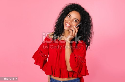 909457386istockphoto Hello, friend! Incredible African American woman in a red blouse and blue jeans is posing with her right hand on her hip and left hand holding a smartphone near her ear. 1182101117