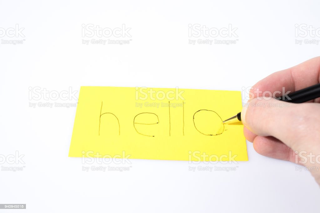 Hello handwrite with a pen and a hand on a yellow paper composition stock photo