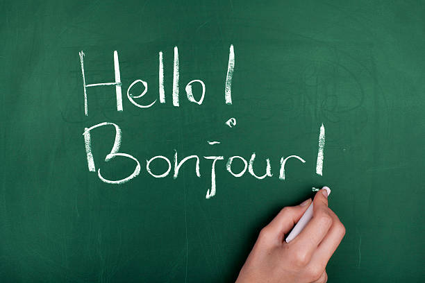 Hello! Bonjour! Woman hand writing ' Hello! Bonjour! ' on green blackboard french culture stock pictures, royalty-free photos & images