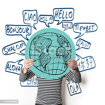 Global communication. Man holding a blue cardboard cut in form of a circle with globe drawn on it. There are many speech bibles drawn on the wall behind him showing the word Hello translated in in many languages