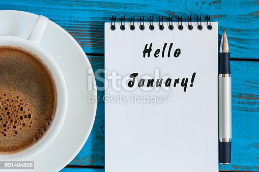 istock Hello January written on paper near morning coffee cup workplace. New year time concept. Business and office background. Top view 891404836
