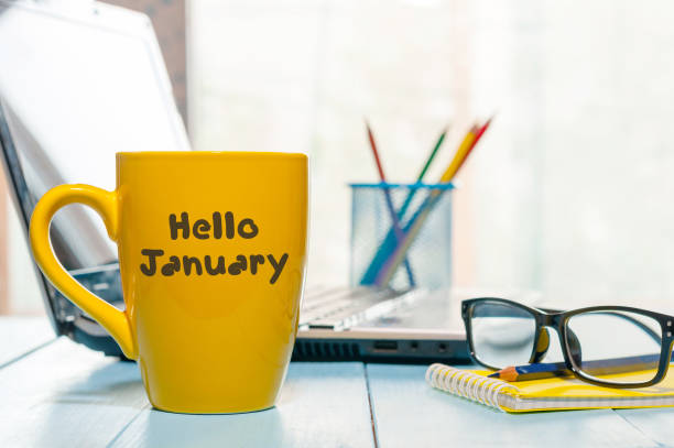 Hello January written on yellow coffee cup at manager or freelancer workplace. New year time concept. Business and office background stock photo
