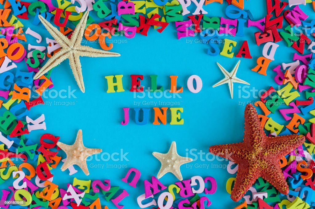 Hello June - word composed of small colored letters at blue background with beach attribute - starfish or five-finger. Summerbeginning and vacation concept stock photo