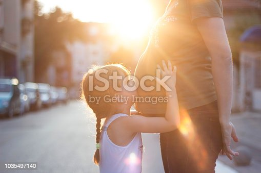 Unrecognizable pregnant woman standing on the street with her four years old daughter embracing and kissing her belly.