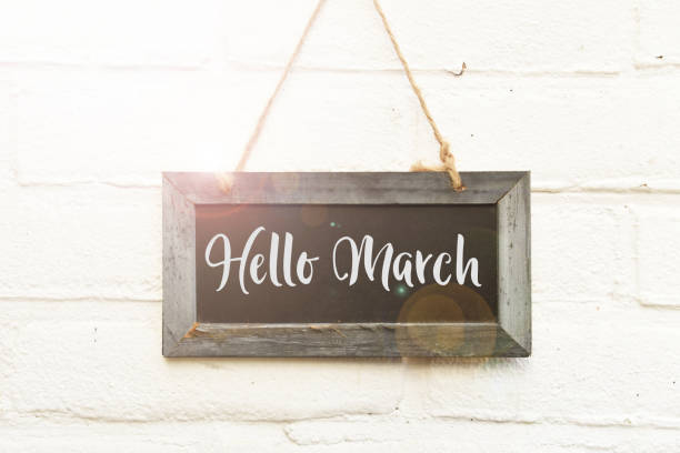 Hello March hand lettering on hanging sign board in spring sunlight stock photo