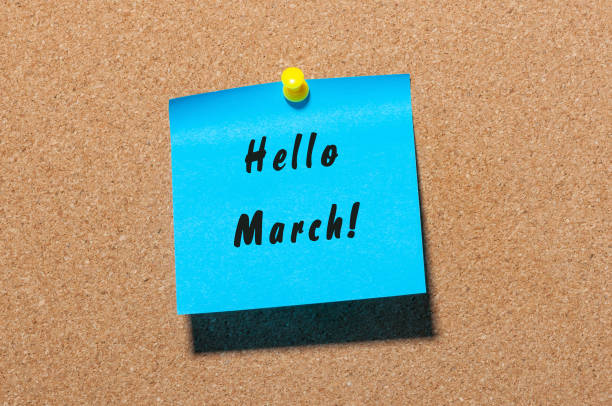 hello march - handwriting on a blue paper pinned at cork noticeboard. beginning of spring concept - welcome march stock photos and pictures