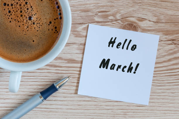 Hello MARCH - note at wooden office table with pen and mug of morning coffee. Spring concept stock photo