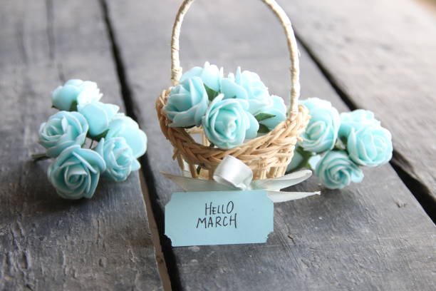 hello march. rustic still life, roses and tag - welcome march stock photos and pictures
