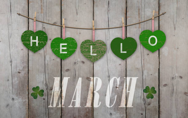 hello march written on hanging green hearts and weathered wooden background - welcome march stock photos and pictures